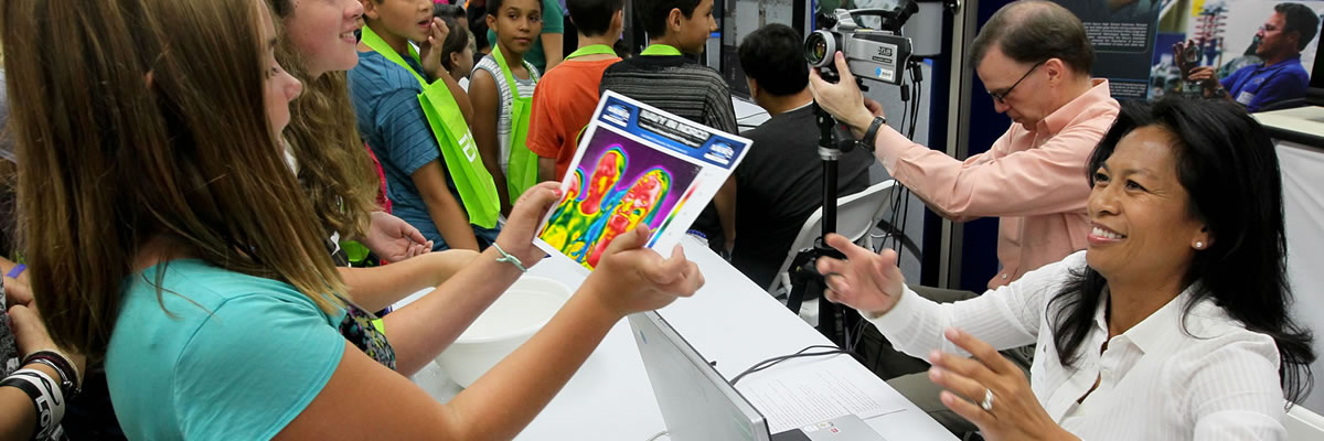 Presenter handing excited student a infrared image of her.